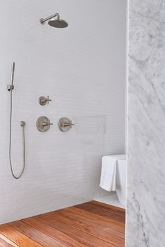 A modern white bathroom with white tiles and a wood shower floor.