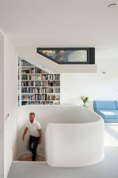 This modern house has a window and a bookshelf that follow the angle of the wall.