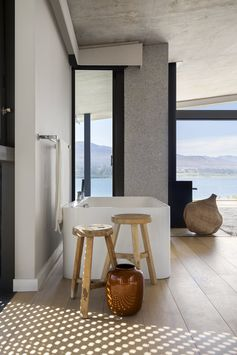 Bath Room, Light Hardwood Floor, Freestanding Tub, and Stone Slab Wall A bathroom that looks out to the lagoon. Photo 13 of 16 in An Elegant South African Home Embraces Mesmerizing Views
