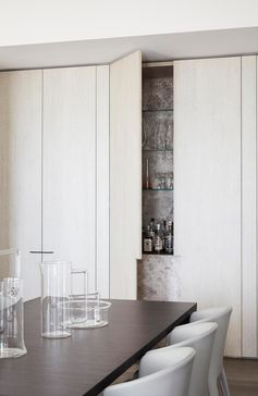 A bar hidden within a minimalist cabinet in the dining room.