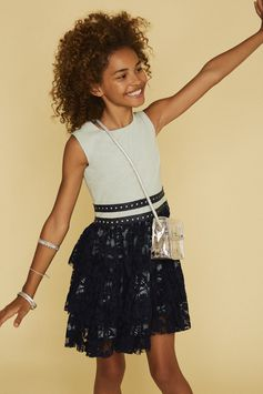 She'll feel all grown up in this sleeveless, floral lace dress accented with striking faux leather trim.