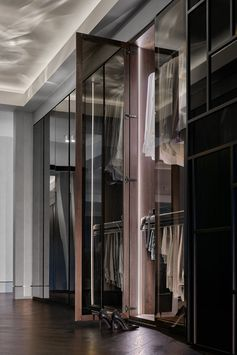 Walk-In Closet - This modern and large walk-through closet has a chandelier and mirrored closets, creating a luxurious space. The closet doors open to reveal hangers and storage space that's highlighted with hidden lighting. #ModernCloset #WalkThroughCloset #ClosetDesign