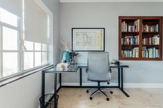 This modern guest bedroom has a workstation with a steel and glass corner desk and a built-in Bookshelf. #HomeOffice #Bookshelf