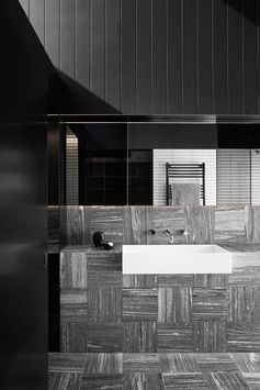This modern black and white bathroom has a grey tile laid in opposite directions adding visual interest to the space. #BathroomDesign #ModernBathroom