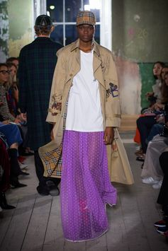 A lilac floor-length skirt in flocked cotton tulle is worn under a neutral-toned gabardine trench coat. Paired with a Vintage check cotton baseball cap and white longline T-shirt with brooch detail.