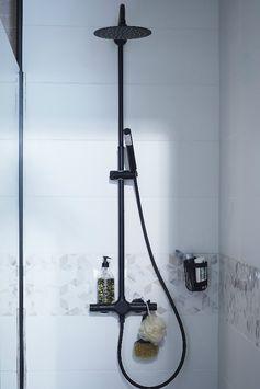 Dans la salle de bains, un rangement à ventouse discret et design complète la déco noir et blanc.