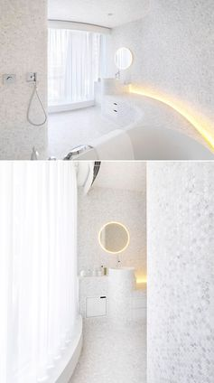 A modern white bathroom with penny tiles, hidden lighting, and curved built-in elements.