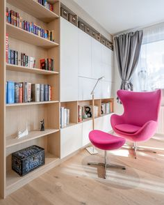 Library Ideas - This modern apartment has a small library area, with bookshelves and a bright pink armchair. #HomeLibrary #ReadingCorner #LibraryIdeas #ShelvingIdeas