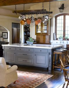 Blue Gray Painted Island: An antique pot rack and an iron lantern over the sink add old-world soul to the kitchen. The island is painted Lamp Room Gray by Farrow & Ball to complement the veining on the Carrara marble countertops.