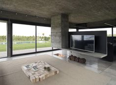 Designed as a sculptural element that separates the dining room and the living room, this modern hanging concrete divider has a chimney built into it on one end, and the other is a platform for holding the television. Underneath, the fireplace has been built into the ground. #Fireplace #RoomDivider #ConcreteDivider #HangingConcreteChimney