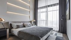 A modern bedroom with an accent wall made from multi-layered sections and hidden lighting