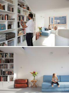 A bookcase that follows the line of the ceiling makes use of an otherwise plan white wall, while a couch helps to create a living room in the open space. #Bookshelf #InteriorDesign #LivingRoom