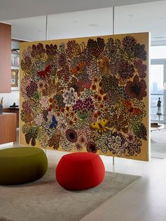 A floating room divider that displays a large tapestry.