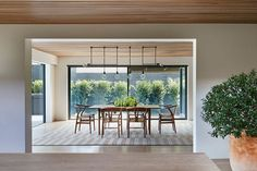 Dining Room Ideas - In this modern and open dining room, plate glass walls add plenty of natural light and views of the garden, while a collection of minimalist lights hang above the dining table. #DiningRoomIdeas #DiningRoom #ModernDiningRoom #GlassWalls #InteriorDesign