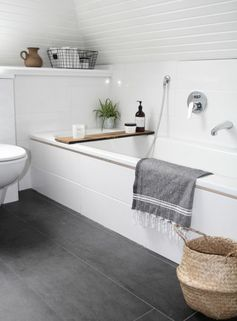 salle de bain avec baignoire blanche et sol carrelage gris