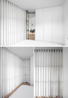Floor to ceiling white curtains create privacy for a glass enclosed bedroom.