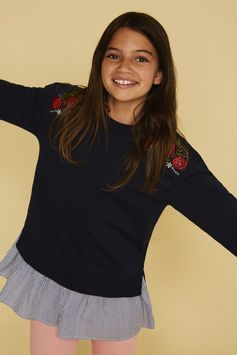 A striped ruffle hem adds a stylish finish to this long sleeve sweatshirt accented with pretty floral embroidery.