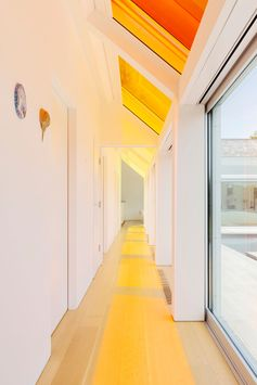 Window Ideas - This hallway is washed with color from the skylights above. In summer, the sliding doors can be opened to allow the breeze to flow through the home, while in winter, the glass facade collects heat from the southern sun, keeping the home warm. #Windows #WindowIdeas #ColorfulWindows #Skylights