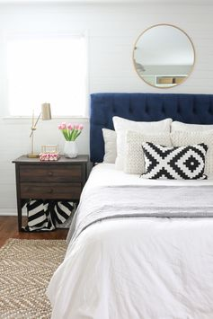 This bright white bedroom space is so calming! Love the white duvet, textured pillows, and navy headboard. Plus the black and white and gold add some serious style to this home space.