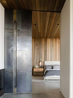 This modern house features a sliding cold-rolled steel plate door that separates the bedroom from the living room. #SteelDoor #ModernInterior