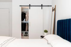 In this modern bedroom, there's a sliding barn door on the closet that includes matte black hardware. Color has been added to the interior with the use of a deep, royal blue velvet headboard and bed frame.