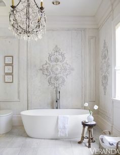 Antique French paneling in Shaw's master bath was refinished in creamy tones for a soft effect. Tub, MTI; fittings, Graff.