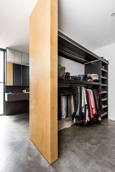 This master bedroom suite has an open walk-in wardrobe that features custom shelving. #WalkInCloset #ClosetDesign