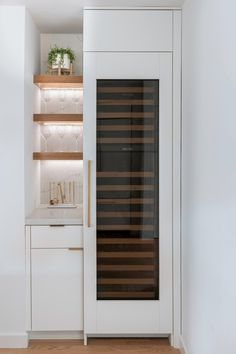 A built-in wine fridge and a small custom designed bar with storage and floating shelves with hidden lighting.