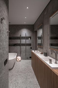 A modern bathroom with a narrow custom-made double sink vanity, a freestanding white bathtub, and a shower with built-in shower niches.