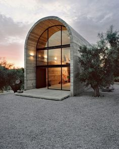Mod Farmhouse with a Cool Curved Roof  This mod farmhouse isn't your typical countryside home. The curved roof gives the house this amazing distinctive silhouette with a striking arched glass wall, flooding interiors with natural light while framing the surrounding view.