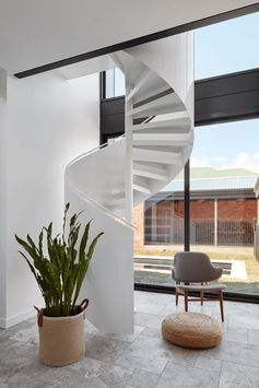 Travertine silver tiles in a French Pattern cover the floor of this modern house extension, and a white Enzie spiral staircase makes a striking statement in the room and leads up to a mezzanine master suite. #SpiralStairs #TravertineFlooring