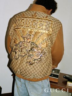 Detailed embroideries including a dragon and appliquéd Gucci cover the back of GG motif jacket from the Gucci-Dapper Dan collection for Fall Winter 2018.
