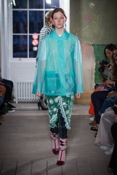 A reimagined waterproof jacket is layered over a white T-shirt, green sleeveless tulle dress and slim tartan high-waisted trousers. This look includes a crystal earring and stud.