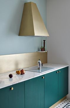 Sitting against a backdrop of mint green walls, the bronze backsplash and range hood in this modern kitchen add a luxurious metallic touch that stands out against the teal cabinets. #KitchenIdeas #BronzeKitchenAccents #TealCabinets #BronzeRangeHood