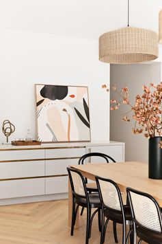 A modern dining area with a wood table, two woven pendant lights, and black-framed dining chairs.