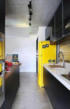 cuisine noire avec grand frigo jaune et plafond brut luminaires noirs style industriel