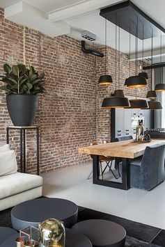 Liefhebbers van industriële interieurs kunnen hun hartje ophalen bij het zien van deze moderne zwarte keuken. Door de hanglampen op verschillende hoogtes te hangen creëer je een speels effect. De massiefhouten keukentafel met stalen onderstel en de steens