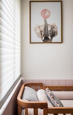 In this modern nursery with a pink palette, a neutral wallpaper with a spotted pattern covers the walls, while fun nursery art in the form of animal prints liven up the space. #ModernNursery #PinkNursery #GirlsBedroom #InteriorDesign #Interiors #NurseryRoom #BabyRoom