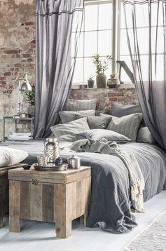Un lit très douillet dans une deco très brute.