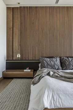 One of the key design choices of this modern bedroom was a large wood slat accent wall that immediately adds a sense of warmth to the room and provides a backdrop for the bed. It's complemented by low profile wood bedside tables, a black headboard, and hanging metallic pendant lights that acts as bedside lamps. #ModernBedroom #BedroomIdeas #WoodAccentWall #WoodSlatWall