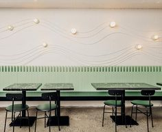 This modern restaurant design uses electrical conduit and keyless lamp fixtures to create attractive wall art that lightly traces the shape of a wave.