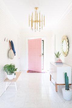 belle entrée pleine de charme décorée de papier peint blanc à pois dorés et aménagée avec une porte rose, un meuble chaussures blanc et un miroir soleil