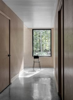 Polished concrete flooring, wood walls and a white ceiling have been combined to create a contemporary interior for this modern cottage. #ConcreteFlooring #WoodWalls