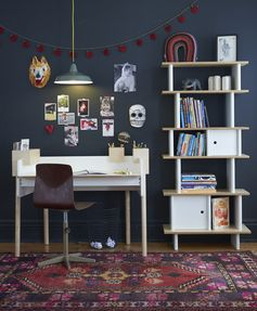 Dark walls, sleek chair, plywood desk, hanging utility light, shelving unit, gallery wall.