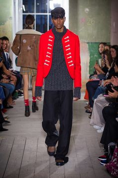 A vibrant red ceremonial jacket with crested buttons with a rib-knit turtleneck sweater and black barathea tuxedo trousers. Leather loafers with fringing and Argyle knitted socks.