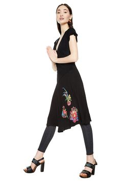Women's black short-sleeved V-neck dress with contrasting floral embroidery. Flared skirt and fitted waist. It´s all about dresses and you can discover Desigual dresses selection on our website.