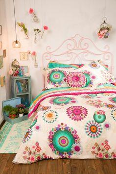 chambre design lit romantique avec des porte plantes aux murs avec des fleurs et des vages porte plantes avec couverture de lit en spirales colorées