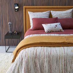 Une parure de lit ethnique chic aux teintes ocre et rouge territe avec parfois un motifs à pois, AM.PM