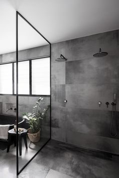 A modern bathroom with a black framed glass shower screen, large format grey tiles, and two shower heads.