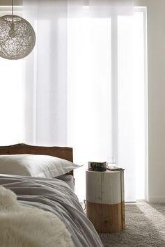 Dans la chambre, une souche de bois brute peinte en blanc pour une table de nuit design.
